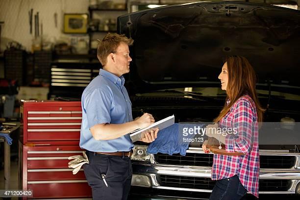 Happy customer discusses repairs with auto mechanic. Repair shop.