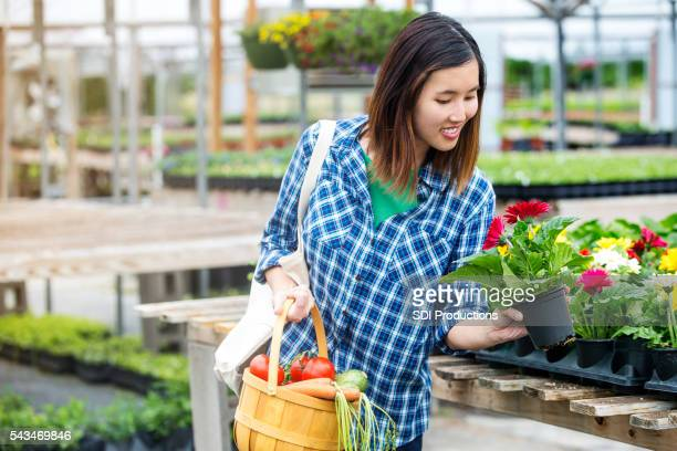 Happy customer shopping for potted plants and fresh summer vegetables