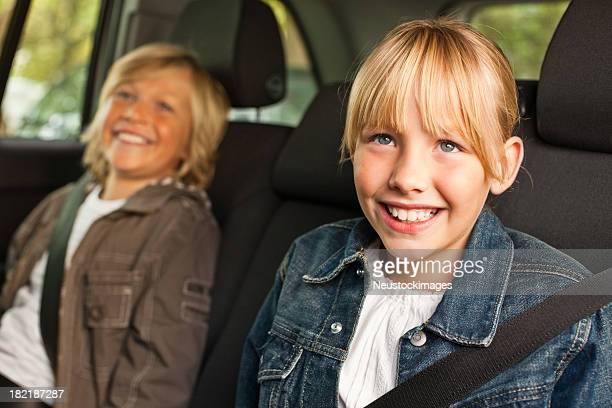 Happy cute boy and girl sitting in a car