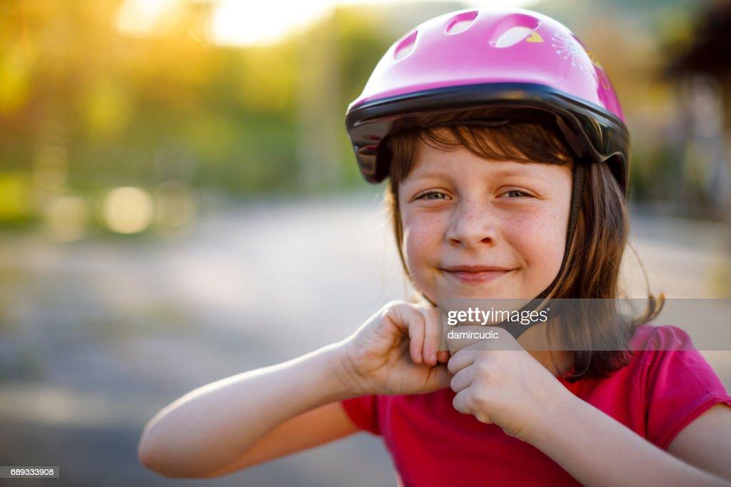 Happy cute girl putting cycle helmet on : Stock Photo