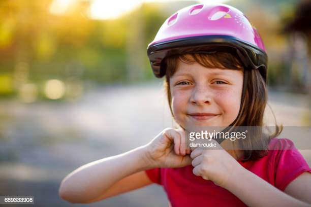 happy cute girl putting cycle helmet on - sports helmet stock pictures, royalty-free photos & images