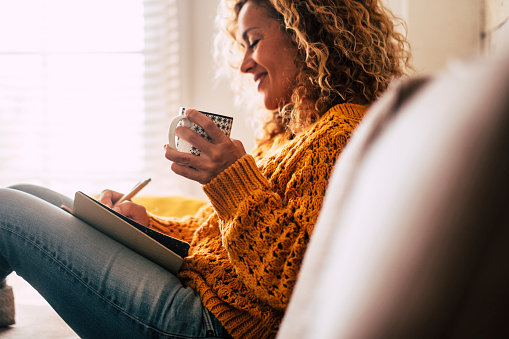 Happy cute lady at home write notes on a diary while drink a cup of tea and rest and relax taking a break. autumn colors and people enjoying home lifestyle writing messages or lists. Blonde curly beautiful lady sit down in the house 1077622726