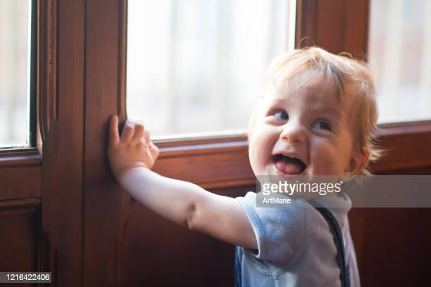 happy cute little boy near the window - blue eyes stock pictures, royalty-free photos & images