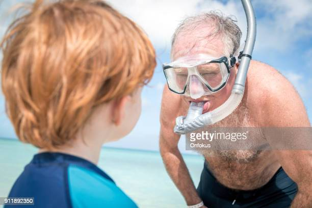 Happy Cute Little Boy Snorkel at Beach with Grandfather