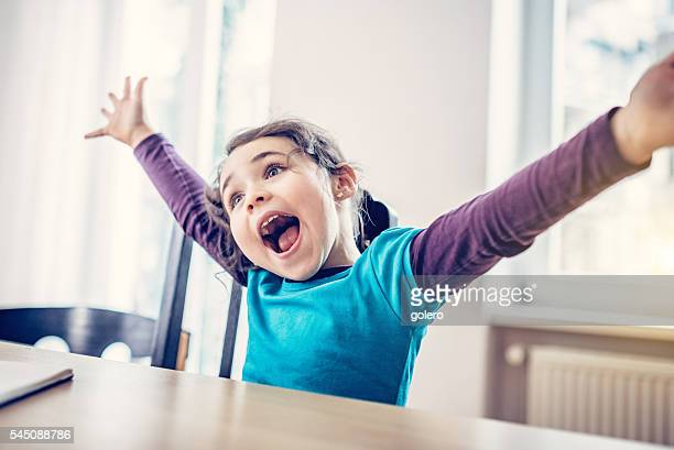 happy cute little girl cheering at desk