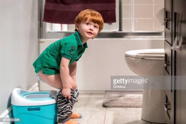 happy cute redhead little boy potty training - kids peeing stock pictures, royalty-free photos & images