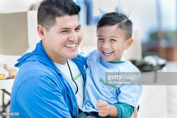 Happy dad and his adorable son volunteer at charity event