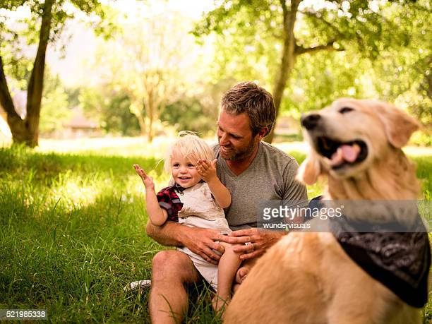 happy dad embracing and holding his son on the legs - one animal stock pictures, royalty-free photos & images