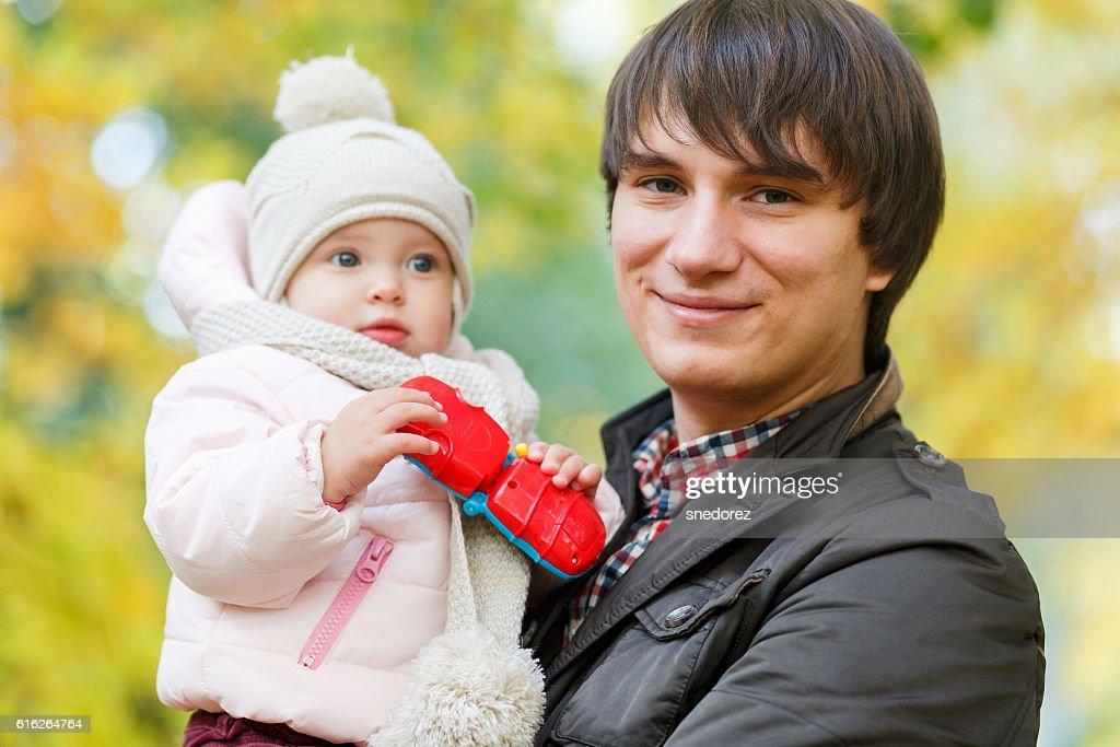 Happy dad holding baby on background of autumn landscape : Stock Photo