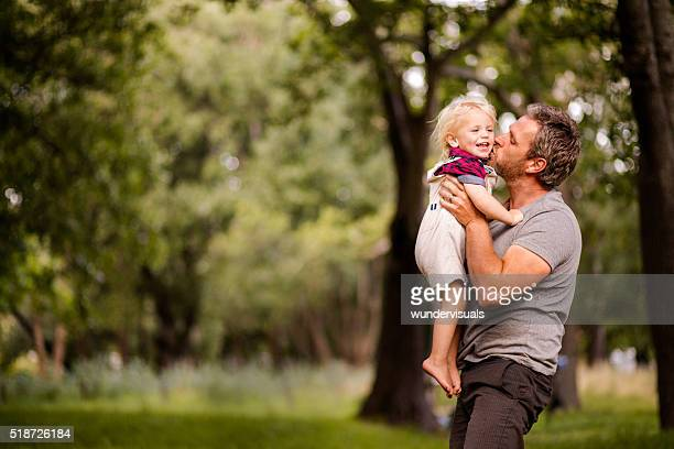 Happy dad kissing his laughing son at the park