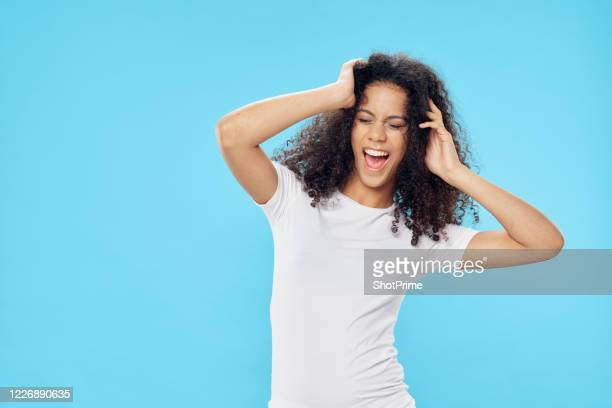 a happy dark-skinned girl with curls on her head in a white t-shirt smiles and holds on to her head and is dancing on a blue background. - vegetais - fotografias e filmes do acervo