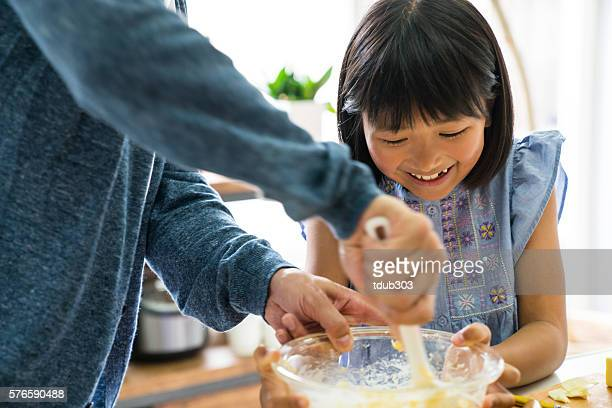 Happy daughter and father baking together on the weekend