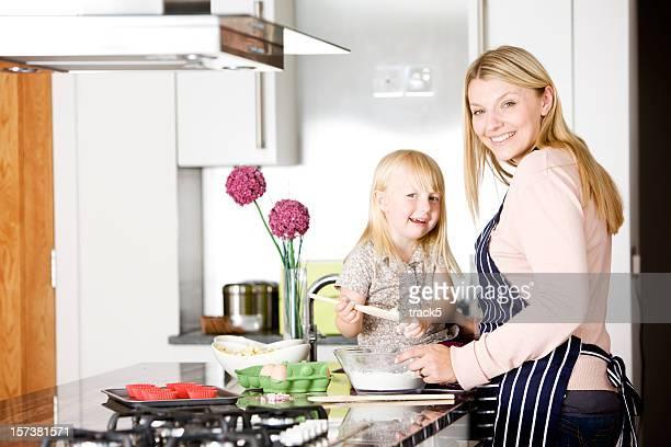 Glückliche Tochter helfen Ihrer Mutter Backen Kuchen in der Küche