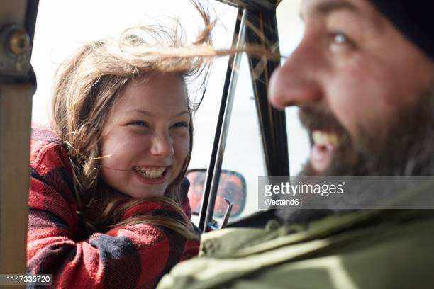 happy daughter looking at father in car - candid stock-fotos und bilder