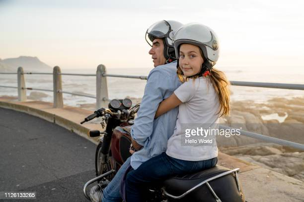 Happy daughter ready to ride on back of motorcycle with dad