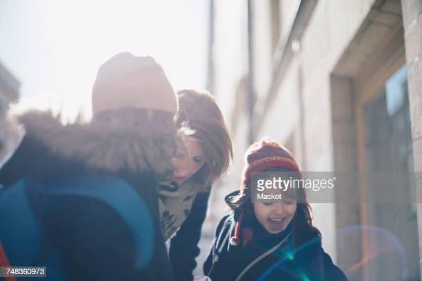 Happy daughters with mother standing in city on sunny day during winter