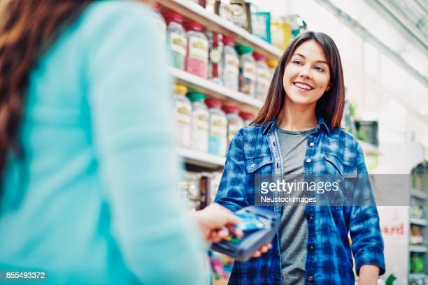 happy deli owner receiving contactless payment from customer - convenience store counter stock photos and pictures