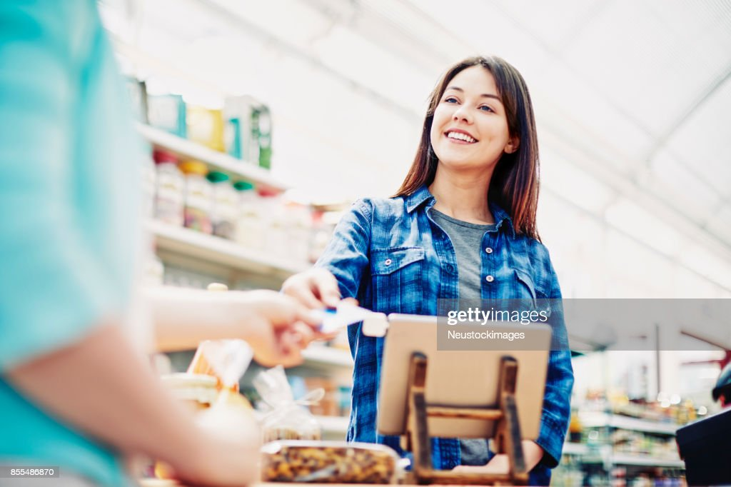 Happy deli owner receiving credit card from customer in store : Stock Photo