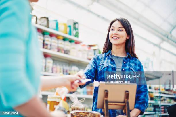 happy deli owner receiving payment through credit card from customer - convenience store counter stock photos and pictures