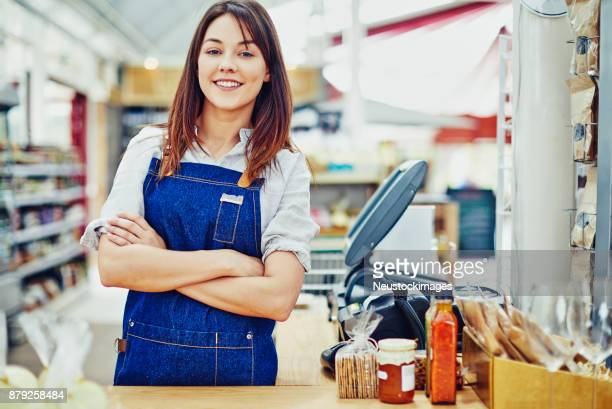 happy deli owner standing arms crossed at checkout counter - convenience store counter stock photos and pictures