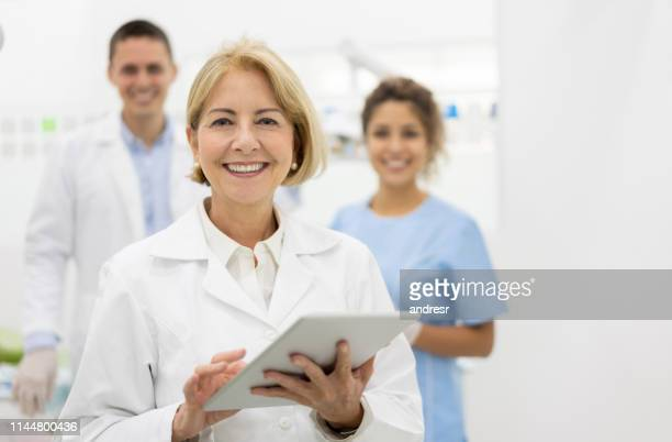 happy dentist at the office with her team and holding a tablet computer - dental equipment stock pictures, royalty-free photos & images