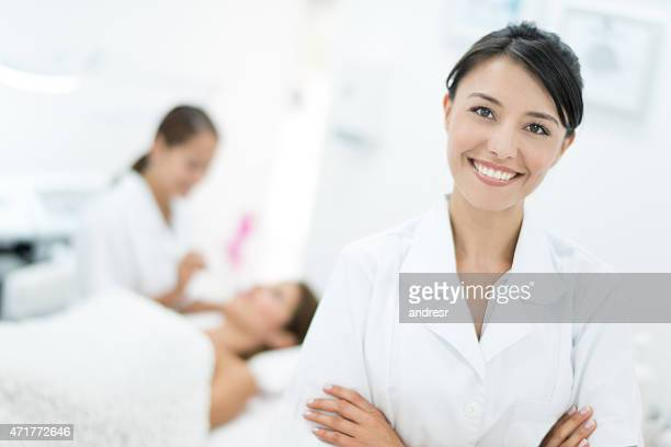 happy dermatologist at her practice - beauty care occupation stock photos and pictures