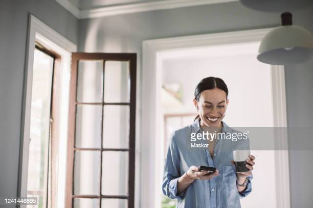 happy design professional with drink and smart phone standing in home office - doorway stock pictures, royalty-free photos & images