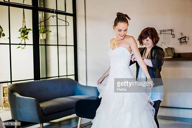 Happy designer assisting bride at bridal shop