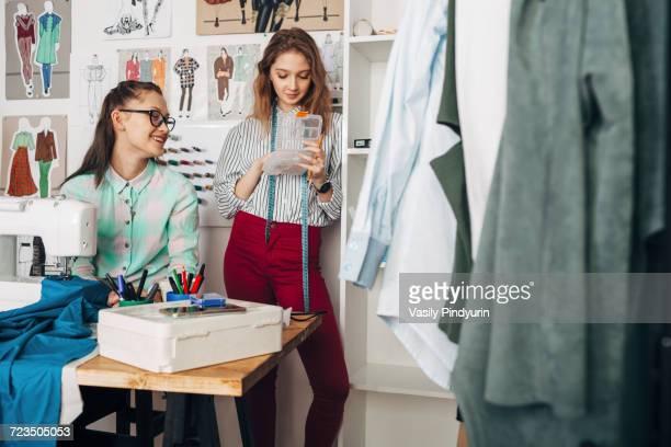 Happy designer looking at female trainee holding container at design studio