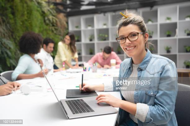 Happy designer working at a creative office using a laptop computer