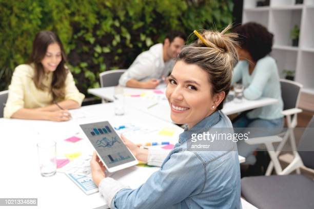 Happy designer working at a creative office using a tablet computer
