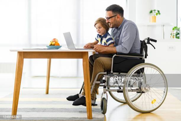 happy disabled father and his small boy using computer at home. - accessibility stock pictures, royalty-free photos & images