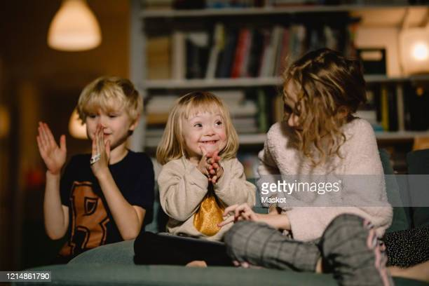 happy disabled girl clapping while sitting with male and female siblings at home - disability stock pictures, royalty-free photos & images
