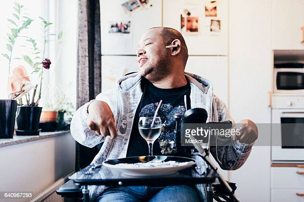 happy disabled musician with drink sitting by window at recording studio - assistive technology stock photos and pictures