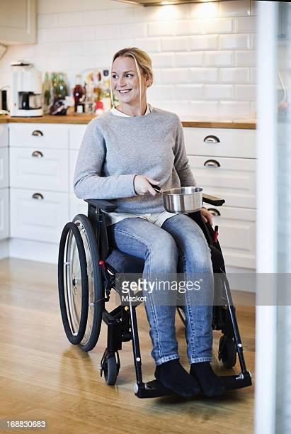 Happy disabled woman in wheelchair looking away while holding saucepan at kitchen