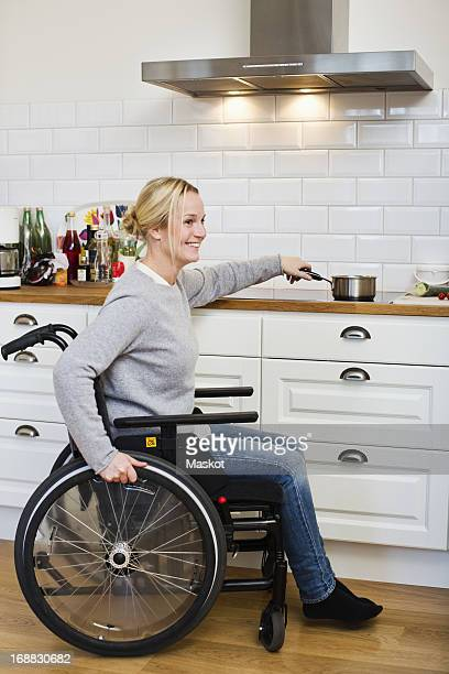 Happy disabled woman in wheelchair preparing tea at kitchen