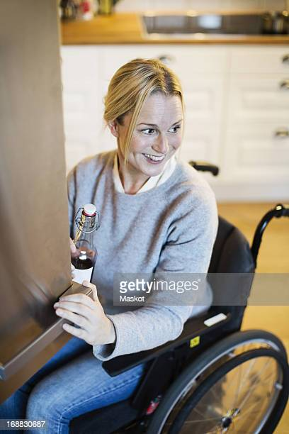 Happy disabled woman with bottle looking away while closing refrigerator's door at kitchen