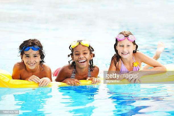 Divers enfants heureux dans une piscine