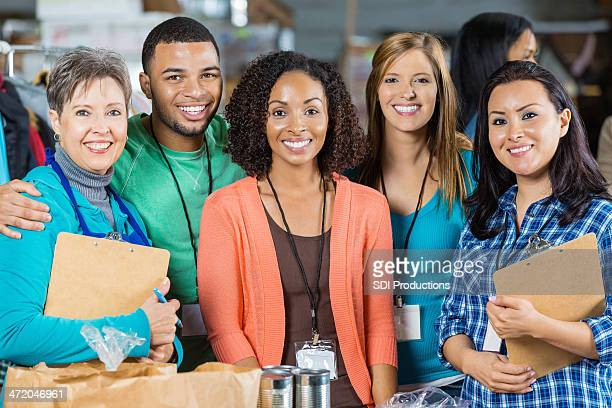 happy diverse group of volunteers at food bank - non profit organization stock pictures, royalty-free photos & images