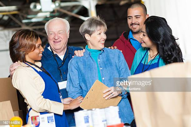 Happy diverse group of volunteers working together in food bank