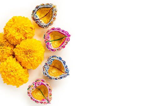 Happy Diwali - Clay Diya lamps lit during Dipavali, Hindu festival of lights celebration. Colorful traditional oil lamp diya with yellow flower on white background 1048539264