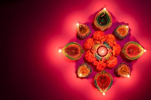 Happy Diwali - Clay Diya lamps lit during Dipavali, Hindu festival of lights celebration. Colorful traditional oil lamp diya on pink background 1177781444
