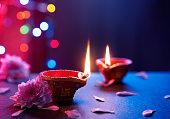 Happy Diwali - Diya lamps on floor with bokeh light background