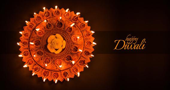 Happy Diwali greeting card design using Beautiful Clay diya lamps lit on diwali night Celebration.  Indian Hindu Light Festival called Diwali, a festival of light 857665646