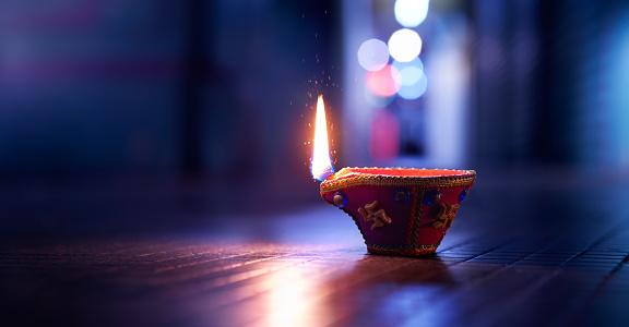Happy Diwali - Lit diya lamp on street at night 1163095779
