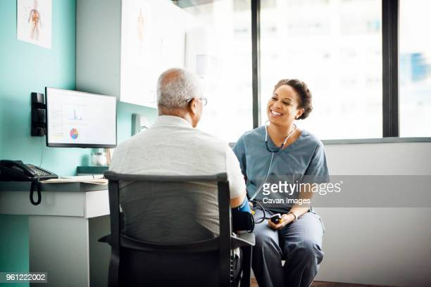 Happy doctor checking male patients blood pressure in clinic