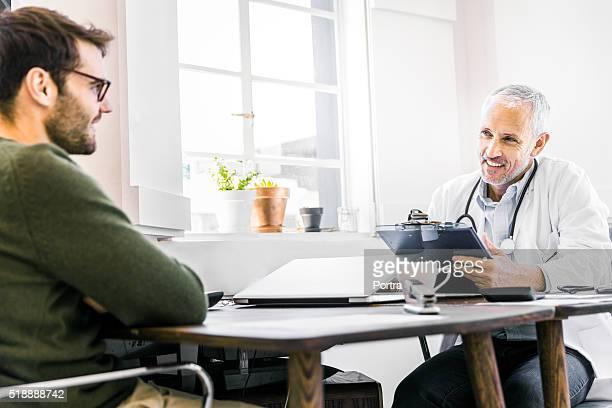 Médico feliz hablando con el paciente en clínica