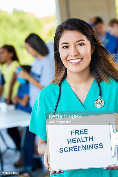"happy doctor holding up """"free health screenings"""" sign - preestreno fotografías e imágenes de stock"