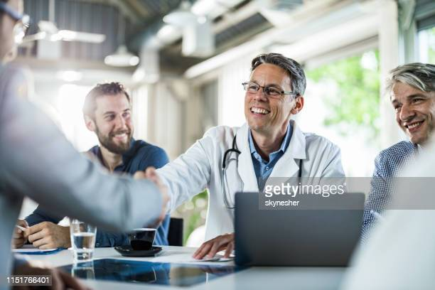happy doctor shaking hands with a businessman on a meeting in the office. - administrator stock pictures, royalty-free photos & images