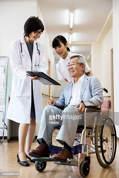 Happy doctor showing record to senior man sitting on wheelchair